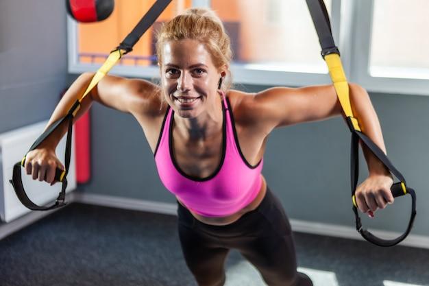Dopasuj młoda blond kobieta ćwiczenia z pasami fitness trx na siłowni. trening fitness dla kobiecego ciała