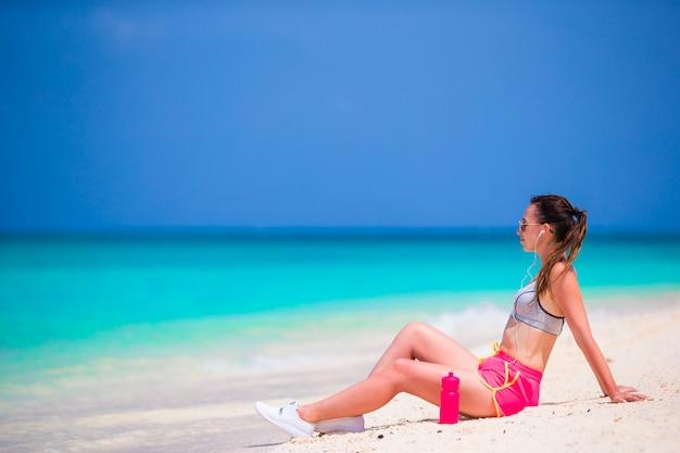 Dopasuj młoda kobieta na tropikalnej plaży biały w jej odzieży sportowej
