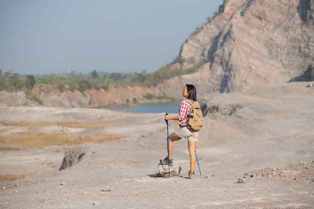 Dopasuj młoda kobieta na wędrówki po górach stojąc na skalistym grzbiecie szczytu z plecakiem i masztem z widokiem na krajobraz.