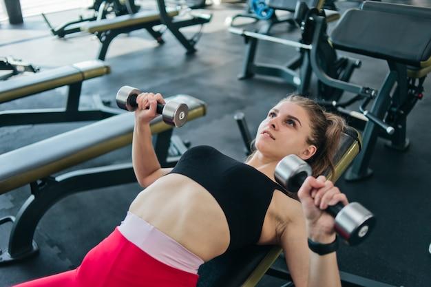 Dopasuj młoda kobieta robi wyciskanie hantli leżąc na ławce skośnej w siłowni