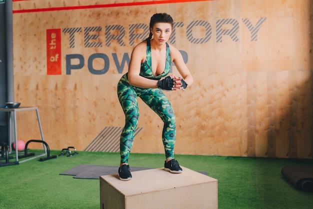Dopasuj młoda kobieta skoki na siłowni w stylu crossfit. lekkoatletka wykonuje skoki na siłowni.
