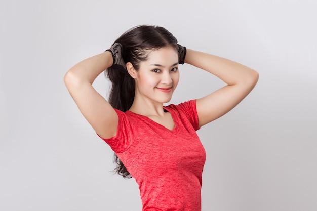 Dopasuj młode piękne zdrowe azjatyckie kobiety z czerwoną odzież sportową i rękawiczki.