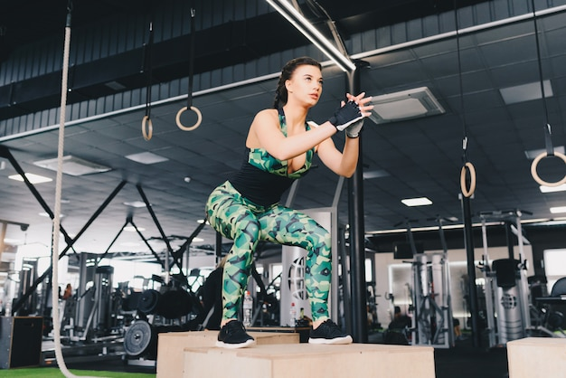 Dopasuj młode sexy kobieta skoki w siłowni w stylu crossfit. lekkoatletka wykonuje skoki na siłowni.