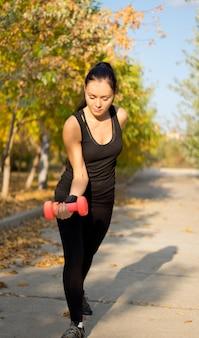 Dopasuj muskularną kobietę, ćwicząc z ciężarami, zginając jej ramię i podnosząc hantle stojąc na wiejskiej drodze