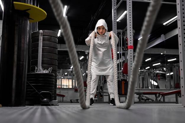 Dopasuj muzułmańską kobietę w sportowym hidżabie, wykonując ćwiczenia crossfit z liną w nowoczesnej siłowni, sam trening arabskiej kobiety, uprawiający sport