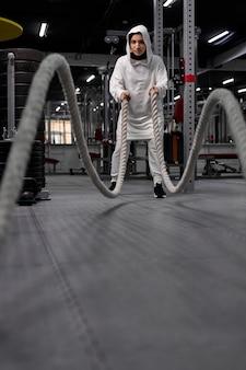 Dopasuj muzułmańską kobietę w sportowym hidżabie, wykonując ćwiczenia crossfit z liną w nowoczesnej siłowni, sam trening arabskiej kobiety, zaangażowany w sport