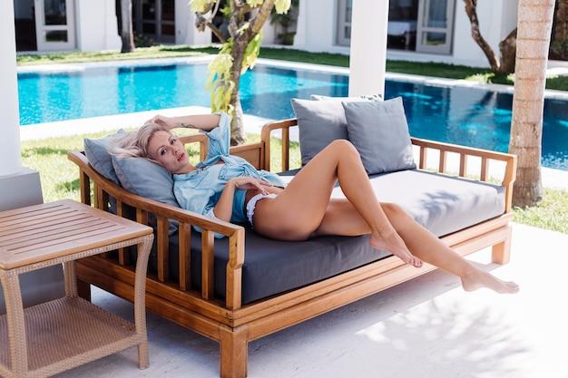 Dopasuj piękną europejską kobietę o krótkich blond włosach w niebieskiej dżinsowej koszuli i białych majtkach bikini