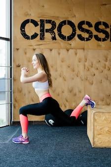 Dopasuj pole młodej kobiety skaczącej na siłowni w stylu crossfit. lekkoatletka wykonuje skoki na siłowni.