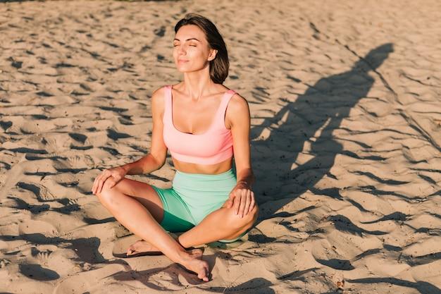 Dopasuj sportową kobietę w idealnej formie o zachodzie słońca na plaży w pozie jogi