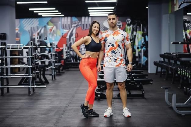 Dopasuj sportowy para stojąc w siłowni i pozowanie. kulturystyka, zdrowe nawyki, fitness indoor