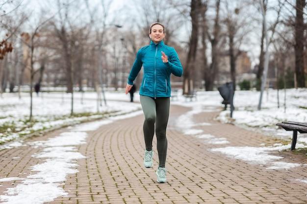 Dopasuj sportsmenka na ścieżce w parku w śnieżny zimowy dzień. rekreacja, śnieżna pogoda, zimowy dzień