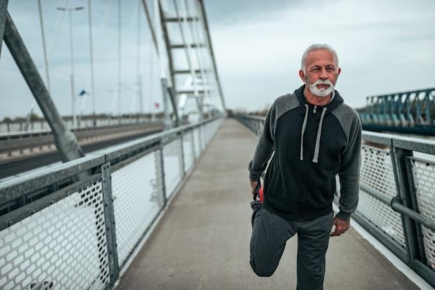 Dopasuj starszego mężczyznę rozgrzewającego się przed ćwiczeniami