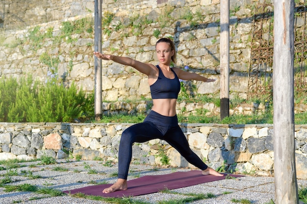 Dopasuj stonowanych młoda kobieta robi drugą pozę jogi wojownika w porannym świetle na zewnątrz