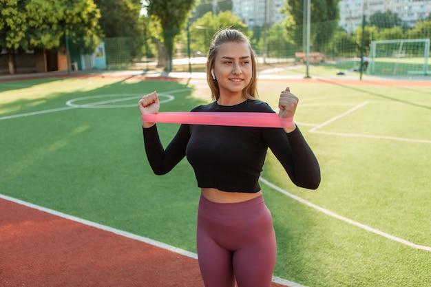 Dopasuj szczupłą kobietę ćwiczącą rozgrzewkę z gumkami fitness na zewnątrz