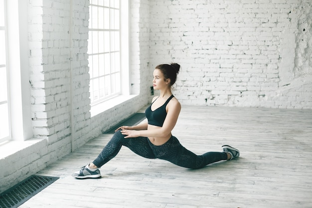 Dopasuj wysportowaną dziewczynę z kok do włosów rozciągających nogi po treningu siłowym w lekkiej przestronnej sali gimnastycznej. piękna młoda kobieta ubrana w modny strój sportowy uprawiająca przednie podziały na podłodze przy oknie