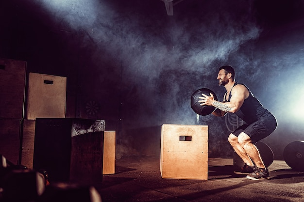 Dopasuj wytatuowany brodaty mężczyzna wskakujący na pudełko w ramach rutynowych ćwiczeń