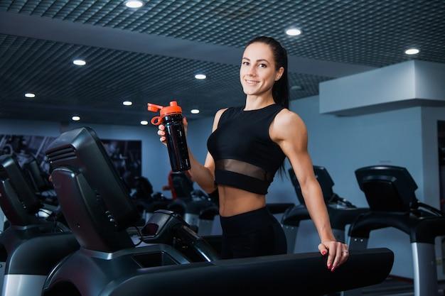 Dopasuj zdrową sportową kobietę robi ćwiczenia cardio na bieżni. lekkoatletka pije wodę z wytrząsarki sportowej w nowoczesnej siłowni