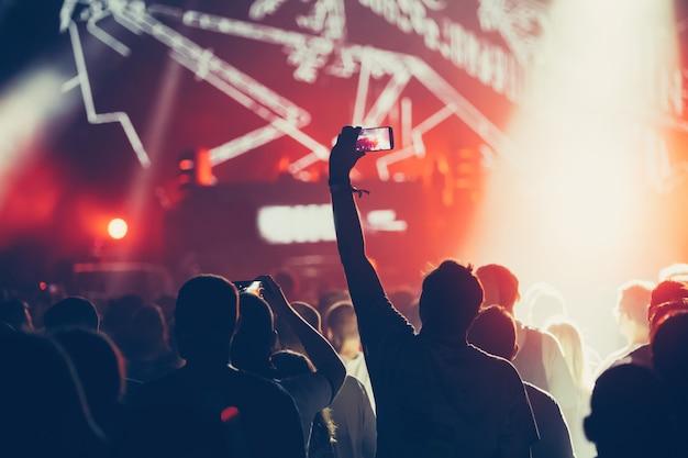 Dopingujący tłum z rękami w powietrzu cieszący się festiwalem muzycznym