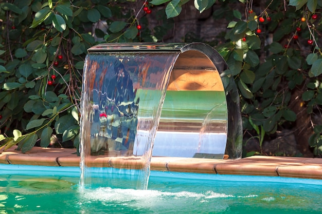 Dopływ wody do basenu przez wodospad. system recyrkulacji i czyszczenia.