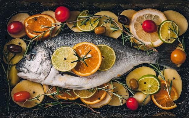 Dorada morska na blasze do pieczenia gotowa do pieczenia z ziemniakami
