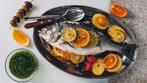 Dorada morska na talerzu pieczona ze smacznym wyborem tropikalnych owoców i warzyw