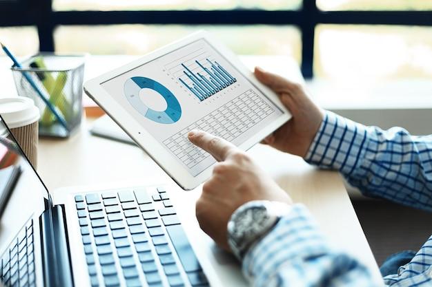 Doradca biznesowy analizujący dane finansowe świadczące o postępach w pracy firmy