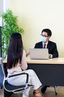 Doradca biznesowy doradza klientowi w sprawie inwestycji. obie osoby miały maski na twarz.