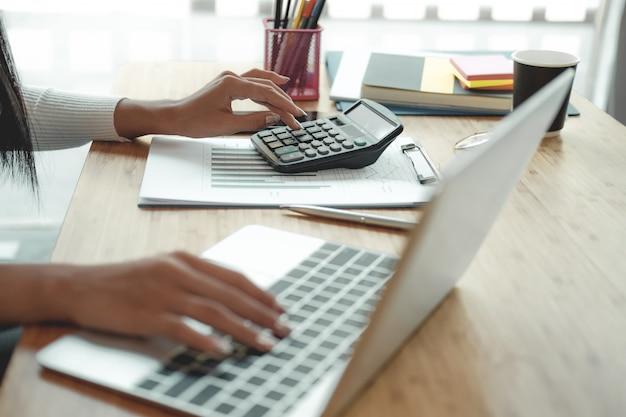 Doradca finansowy korzysta z kalkulatora do obliczania dochodów i budżetu. księgowy prowadzący księgowość. księgowy dokonywania obliczeń