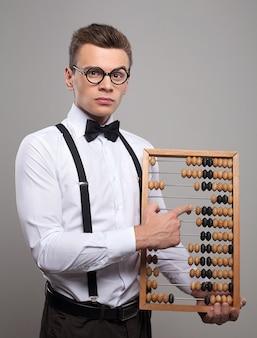 Doradca finansowy. poważny młody człowiek w muszce i szelkach, trzymający liczydło i wskazujący go, stojąc na szarym tle