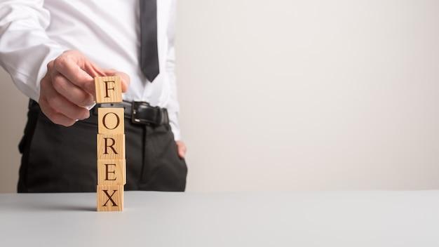 Doradca finansowy, tworząc stos drewnianych klocków pisowni forex