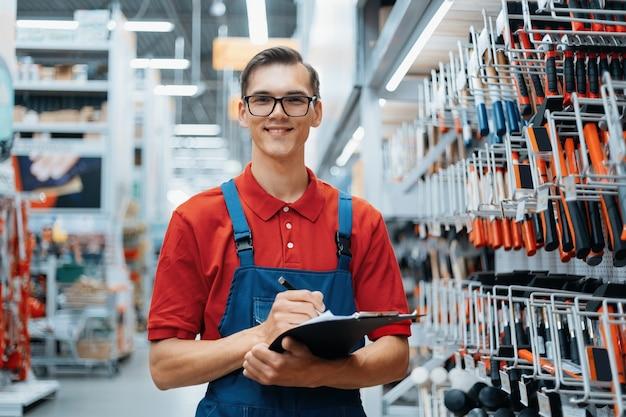 Doradca w sklepie z narzędziami robi notatki o dostępności towaru na półkach