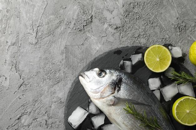Dorado ryba, wapno, rozmaryn i lód na szarym tle, odgórny widok