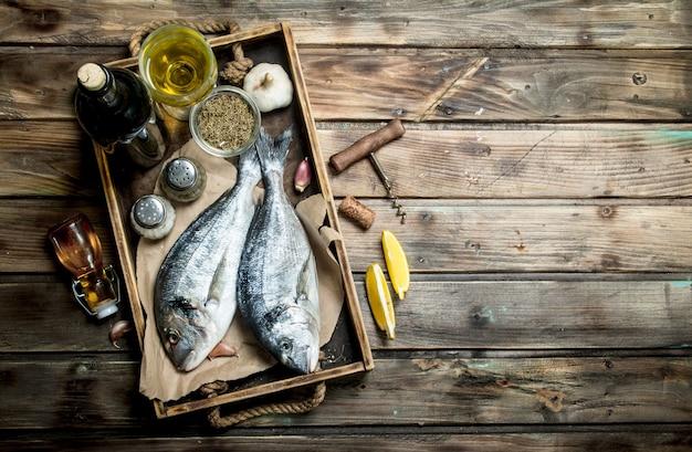 Dorado z surowej ryby morskiej z przyprawami i białym winem. na drewnianym tle.