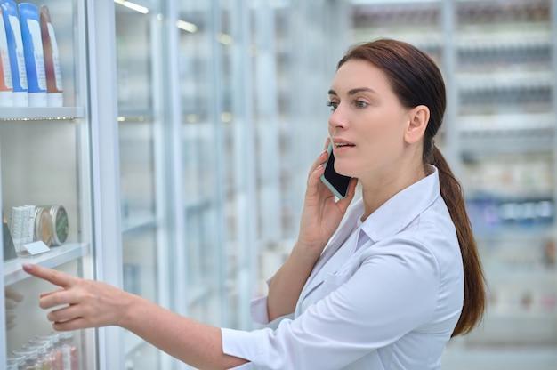 Doradztwo telefoniczne. uważna zaangażowana farmaceutka z długimi ciemnymi włosami konsultuje się za pomocą smartfona stojącego w pobliżu półek z lekami w aptece