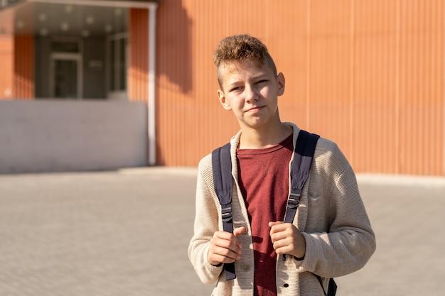 Dorastający chłopiec z plecakiem stojący przed budynkiem szkoły