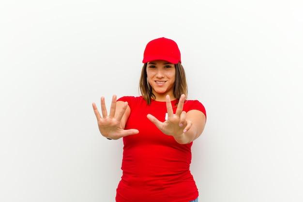Doręczeniowa kobieta uśmiechnięta i patrzeje życzliwą, pokazuje liczbę osiem lub ósmy z ręką naprzód, odliczający przeciw bielowi