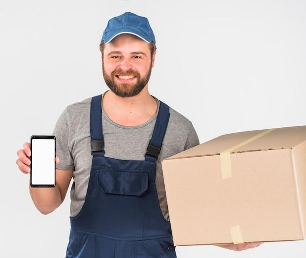 Doręczeniowego mężczyzna mienia pudełko i smartphone z pustym ekranem
