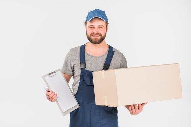 Doręczeniowego mężczyzna pozycja z pudełkiem i schowkiem