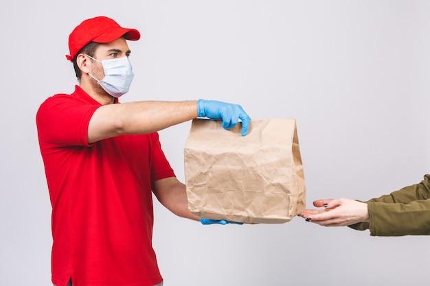 Doręczeniowego mężczyzna pracownik w czerwonej nakrętki koszulki munduru twarzy maski pustych rękawiczkach trzyma pustego karton odizolowywającego na biel ścianie. usługa kwarantanna pandemiczny wirus koronawirusa koncepcja 2019-ncov.