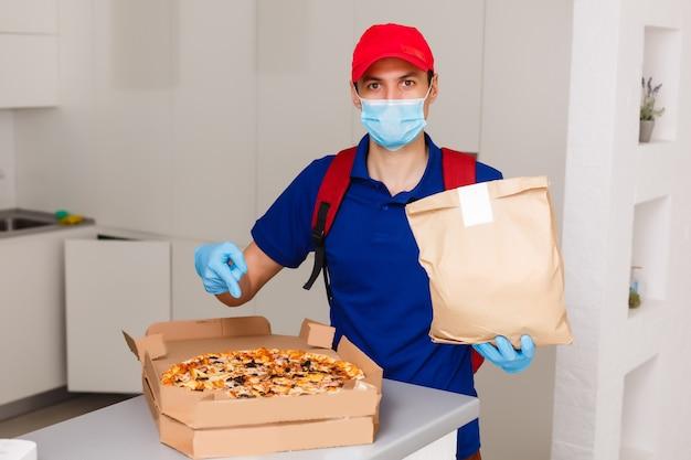 Doręczeniowego mężczyzna pracownik w czerwonych nakrętki koszulki munduru maski rękawiczkach daje karmowego rozkazu pizzy pudełkom odizolowywającym na żółtym tła studiu. usługa kwarantanny pandemicznego wirusa koronawirusa grypa 2019-ncov koncepcja