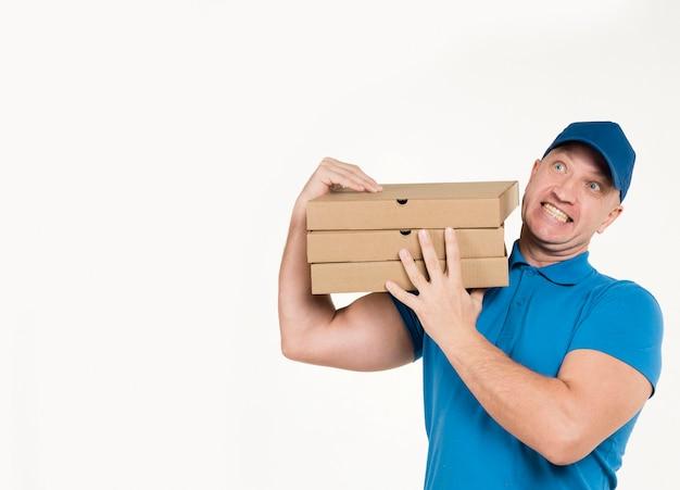 Doręczeniowego mężczyzna przewożenia pizzy pudełka z kopii przestrzenią