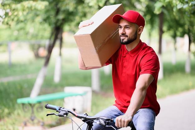 Doręczeniowego mężczyzna przewożenia pudełko na rowerze