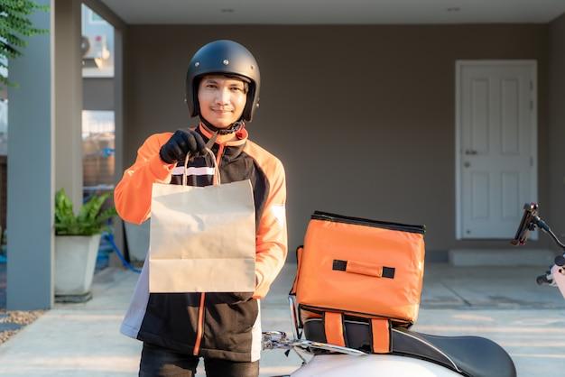 Doręczeniowy azjatycki mężczyzna jest ubranym pomarańcze mundur i przygotowywa wysyłać dostarczającą karmową torbę przed klient houes z karmowym skrzynki pudełkiem na hulajnoga, ekspresowej karmowej dostawie i robić zakupy online pojęcie.