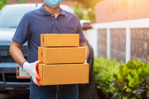 Doręczeniowy azjatykci mężczyzna trzyma kartony w medycznych gumowych rękawiczkach i masce. zakupy online i dostawa ekspresowa lub e-commerce. koncepcja zapobiega rozprzestrzenianiu się zarazków i zapobiega infekcjom covid-19