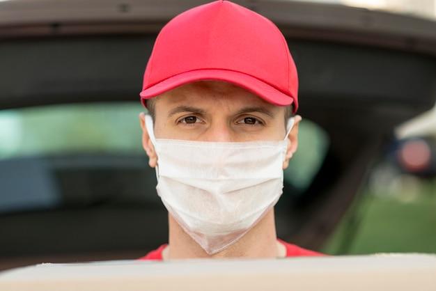 Doręczeniowy facet jest ubranym maskowego zakończenie