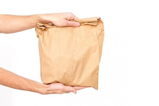 Doręczeniowy facet trzyma papierową torbę i schowek odizolowywający na białym tle