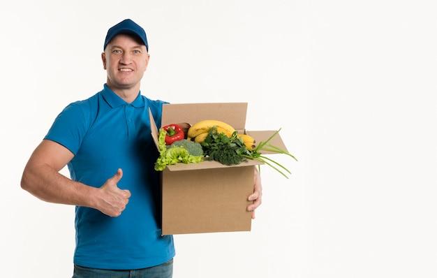 Doręczeniowy mężczyzna daje aprobatom i trzyma pudełko spożywczego
