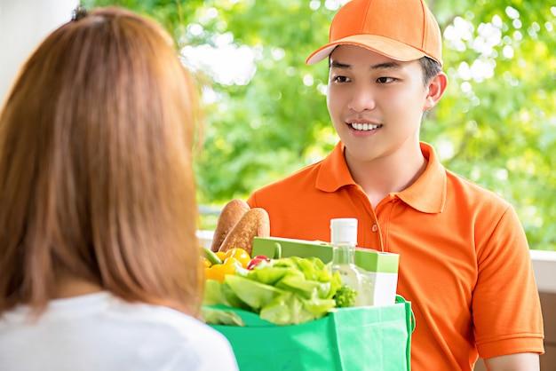 Doręczeniowy mężczyzna dostarcza jedzenie kobiecie w domu