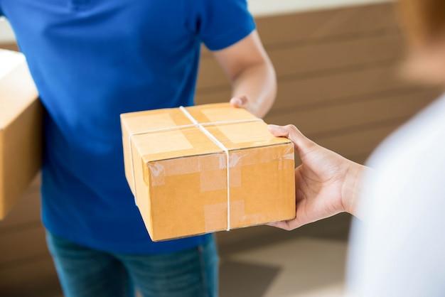 Doręczeniowy mężczyzna dostarcza paczkę kobiecie