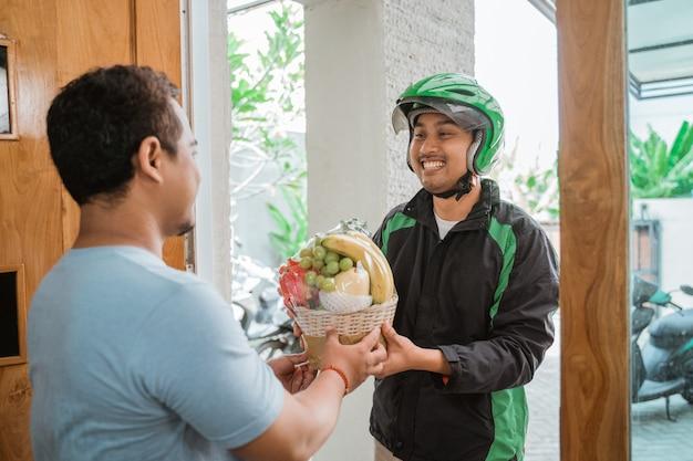 Doręczeniowy mężczyzna dostarcza paczkę owocową